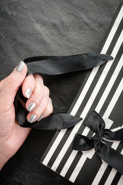 Female hand holding a package in white and black stripes with a bow close-up