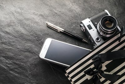 Phone, camera, pen in a black bag with white strips free space