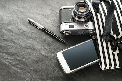 Phone, camera, pen in a black package with white stripes with the right