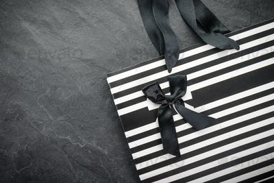 White package in black stripe with handles ribbons and black bow free space