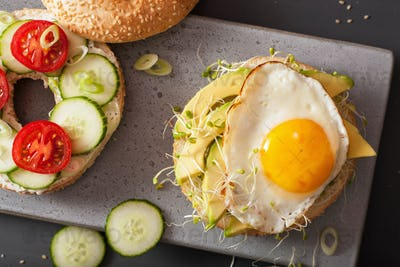 sandwiches on bagels with egg, avocado, soft cheese, tomato, cuc
