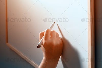 Female businessperson writing on whiteboard