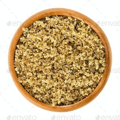 Dried elderflowers in wooden bowl over white