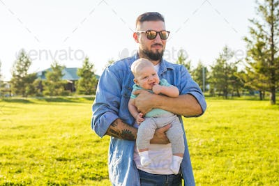 Happy father holding baby son. Concept of happy family, father's day and child.