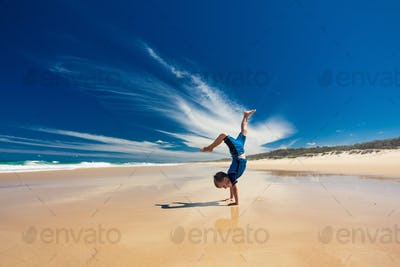 Acrobatic young boy performing hand stand on the beach