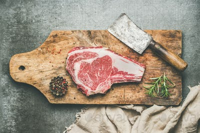 Meat dinner concept with raw beef steak rib-eye with seasoning