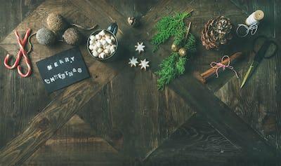 Flat-lay of greeting card, glittering toys, hot chocolate, cinnamon, scissors