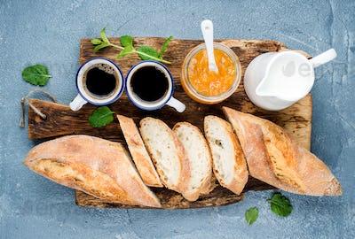 Breakfast set. Baguette, orange jam and coffee in cups