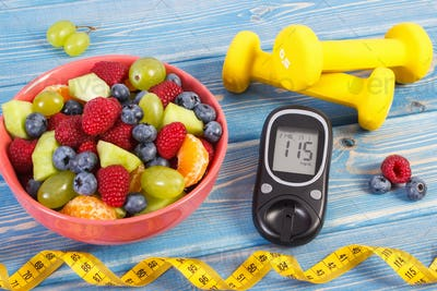 Fresh fruit salad, glucometer, centimeter and dumbbells, diabetes