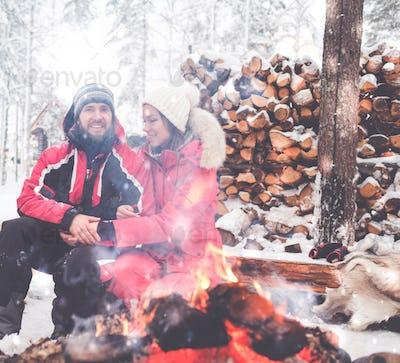 Couple near bonfire in winter landscape