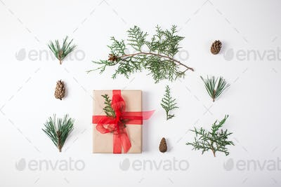 Christmas composition. Gift, christmas decoration, cypress branches, pine cones on white background