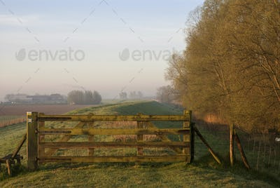 Closed gate on a dyke on a misty morning near the Dutch village Werkendam