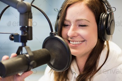 Jockey Smiling While Using Headphones And Microphone In Radio St