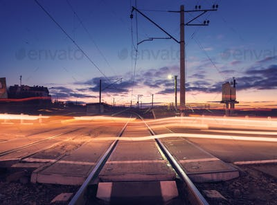 Railroad crossing with car lights in motion at night