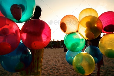 Girl on beach with colorful balloons.