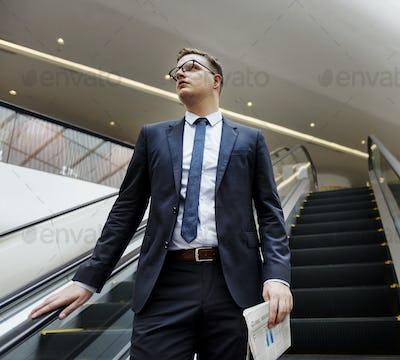 Business Man Walking Down Escalator Concept