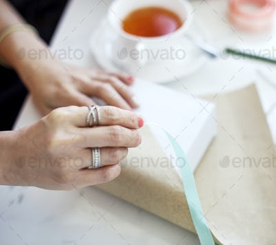 Hands are wrapping gift box