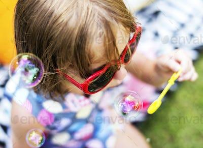 Young girl enjoying blowing soap bubbles