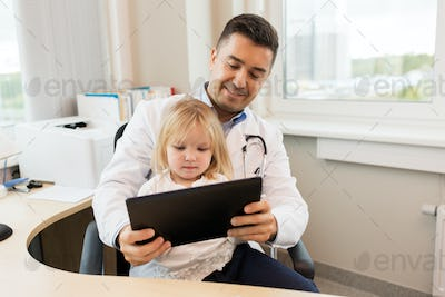doctor and little girl with tablet pc at clinic