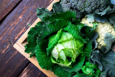 Variety of cabbages in wooden basket on brown background. Harvest. Top view.