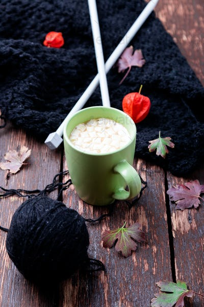 Cup of coffee or hot chocolate with marshmallow near knitted blanket and knitting needles.
