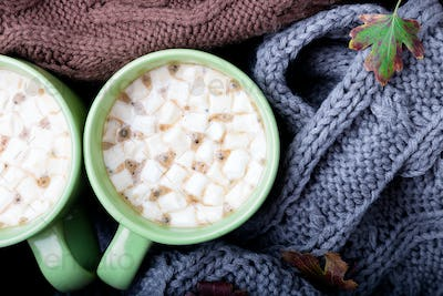 Two cup of coffee or hot chocolate with marshmallow near three knitted weater or  knitted blanket.