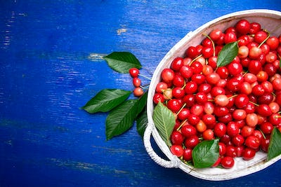 Red cherries in white basket on blue wooden background. Cherry close up. Top view. Copy space.