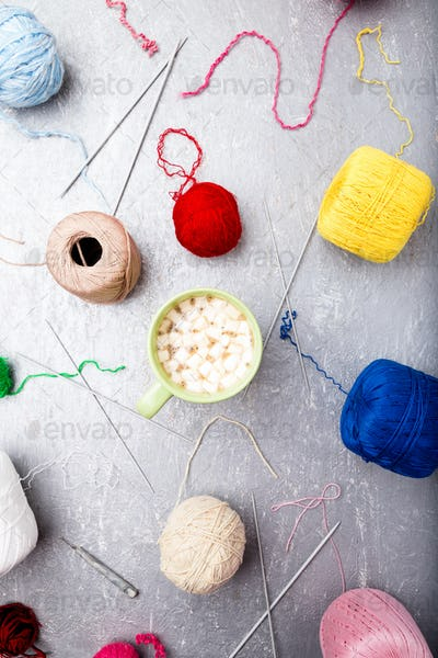 Multicolor knitting ball and needles around green cup of coffee