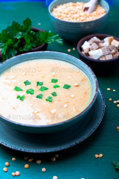 Pea soup in green bowl on green wooden background. Top view. Dry yellow pea. Vegan food.