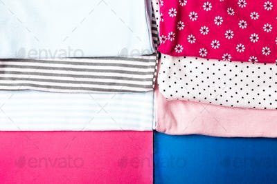 Fabric Sewing. Folded blue and pink bodysuit.  Stack of infant clothing