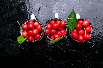 Cherry in enamel cup on black background. Healthy, summer fruit. Cherries. Top view.