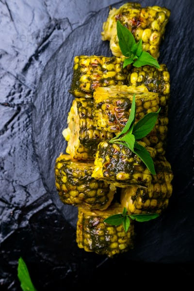 Grilled corn with sauce pesto on black slate plate. Top view. Vegan food.