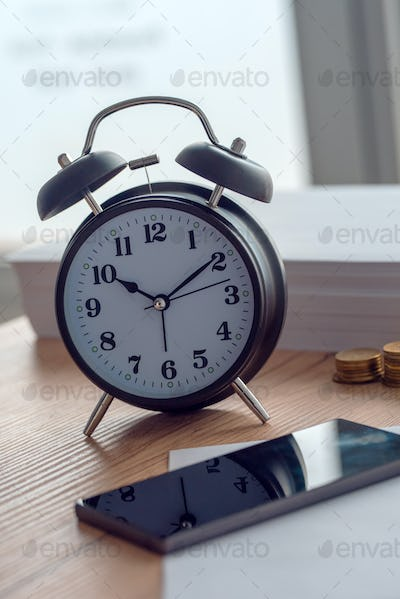 Working hours, vintage clock and mobile phone