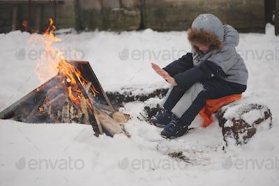 boy sitting by fire in the street