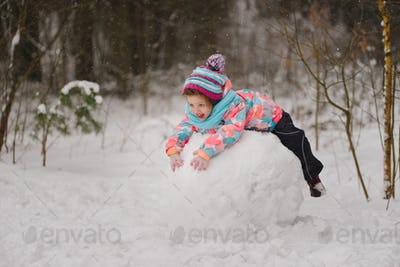 girl makes snowman in winter park