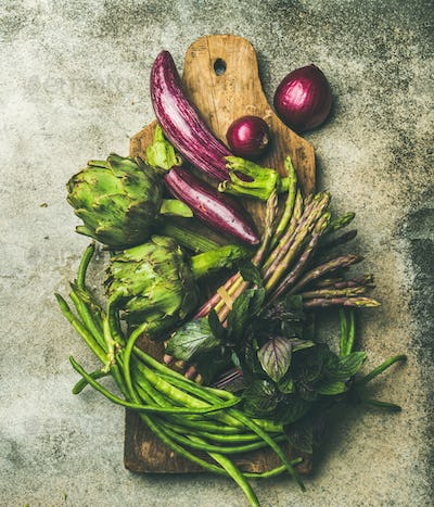 Flat-lay of green and purple vegetables on board, grey background