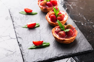 Homemade strawberries tarts on slate plate, black background
