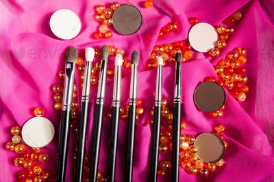 Make up brushes with other cosmetic products on pink veil