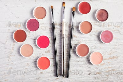 Cosmetics and make up products and accessories on white wooden background