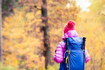 Hiking woman with backpack looking at inspirational autumn golde