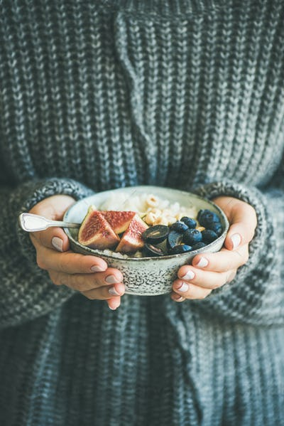 Woman in woolen sweater holding bowl of rice coconut porridge