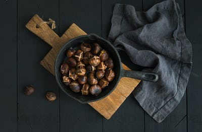Roasted chestnuts in iron skillet pan on rustic wooden board