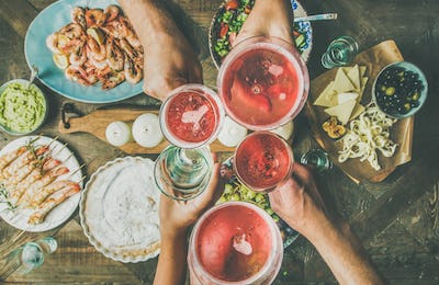 Flat-lay of friends hands eating and drinking together, horizontal composition