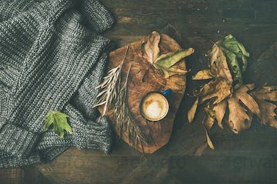 Autumn morning coffee concept with leaves and grey sweater