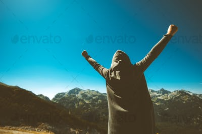 Victorious female person on mountain top.