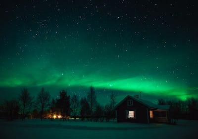 Northern lights (Aurora Borealis) over  cottage in Lapland village. Finland