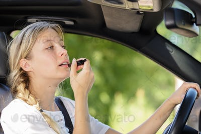 young woman putting lipstick in the car