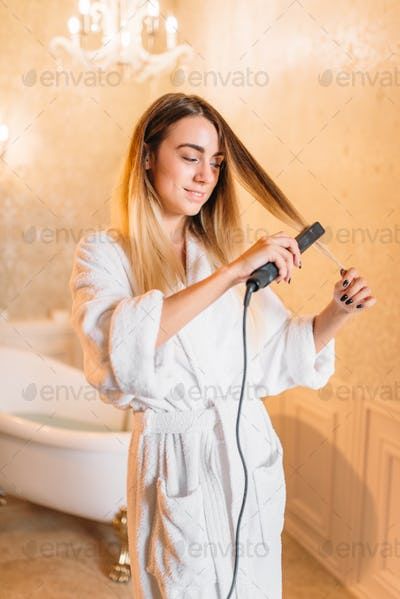 Woman with curling iron, bathroom on background