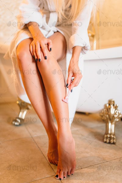 Female person shaves legs in bathroom