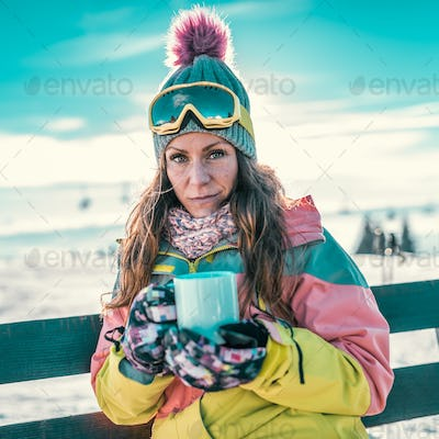 Woman with cup of coffee or tea enjoying the winter day on mount